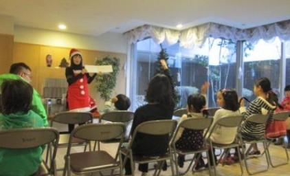 サンタさんになった先生が読み聞かせ中です。